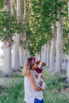 Молодая красивая женщина, держа ее милая маленькая собака на открытом воздухе и целуя ее собаку. любовь к животным концепции и образ жизни на открытом воздухе