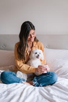 Женщина и ее милая собака дома пьют чай