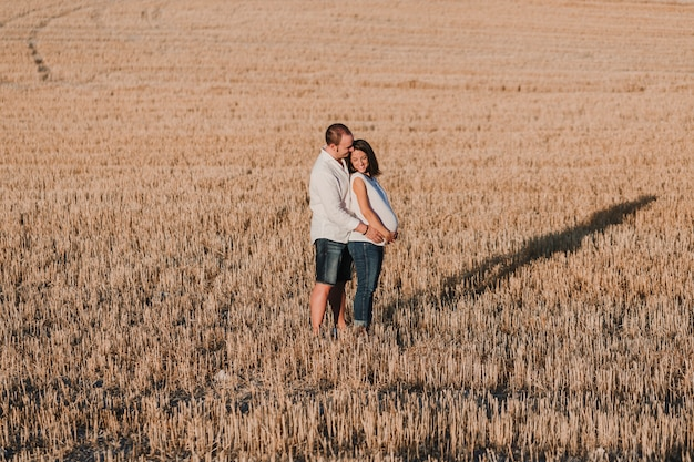 Портрет на открытом воздухе молодой молодой беременной пары в желтом поле. на природе семейный образ жизни.