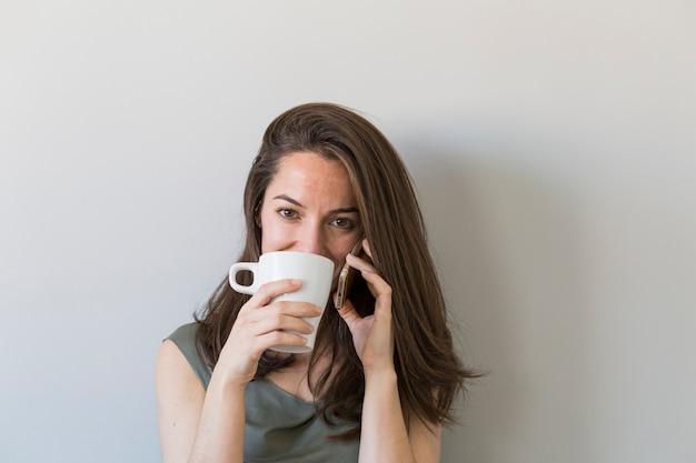 ベッドでコーヒーを楽しんで、彼女の寝室でスマートフォンで話している美しい若い女性