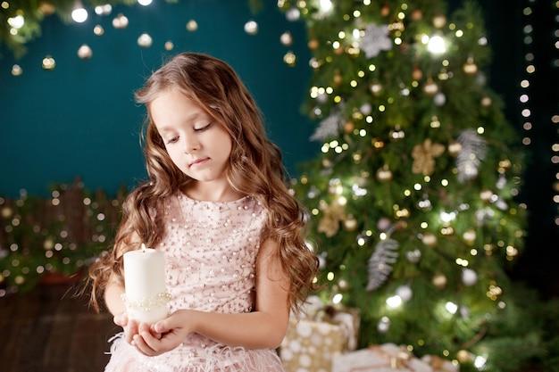 ライトのドレスでかわいい長髪の少女の肖像画。燃えているろうそくを保持している小さな女の子。クリスマス、新年。