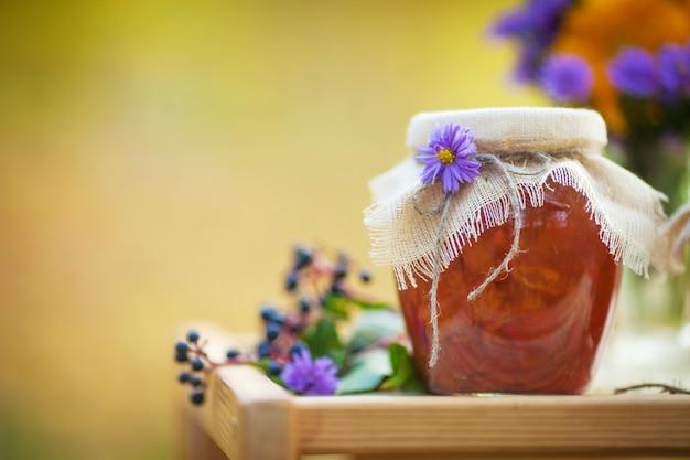 テーブルの上のおいしいアプリコットジャムとガラスの瓶。秋の時間