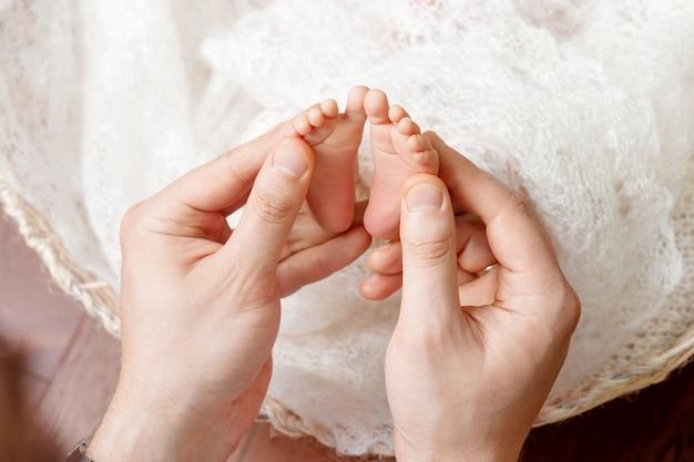 小さな赤ちゃんの足をマッサージする父または医者。生まれたばかりの子供の足を手で優しく保持している父。幸せな家族 。