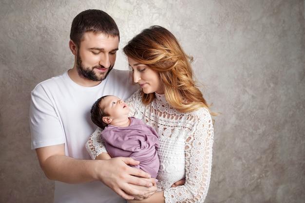 女と男が新生児を保持しています。お母さん、お父さん、赤ちゃん。手に新生児と笑顔の家族の肖像画。コピースペース
