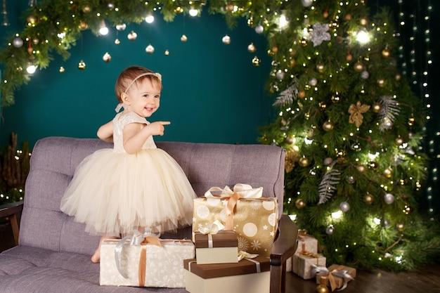 Хорошенькая девочка в белом платье играет и радуется о рождественских огнях