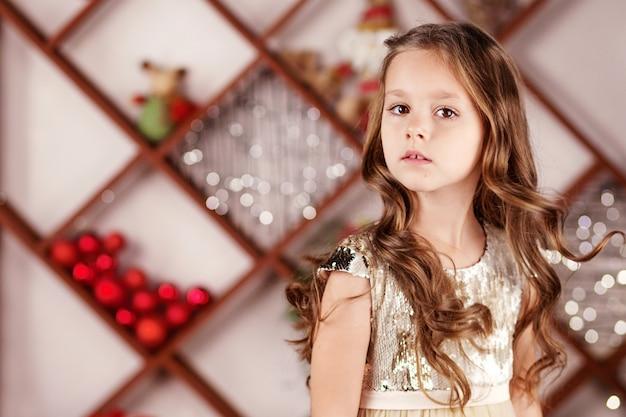 Портрет милая длинноволосая маленькая девочка в платье на фоне рождественских огней