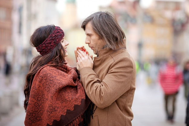 都市の古い広場でポーズをとって幸せなカップル。かなり美しい女性と彼女のスタイリッシュな男が路上でハグします。秋または冬時間。