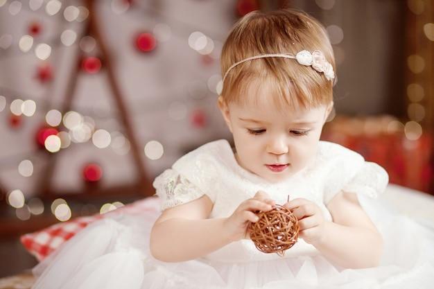 新年とクリスマスのお祝いのコンセプト。再生とクリスマスツリーとライトについて満足している白いドレスのかわいい女の子。冬休み。