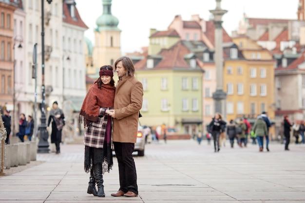 都市の古い広場でポーズをとって幸せなカップル。かなり美しい女性と彼女のハンサムなスタイリッシュな男が路上でハグします。秋または冬時間。ワルシャワ、ポーランド