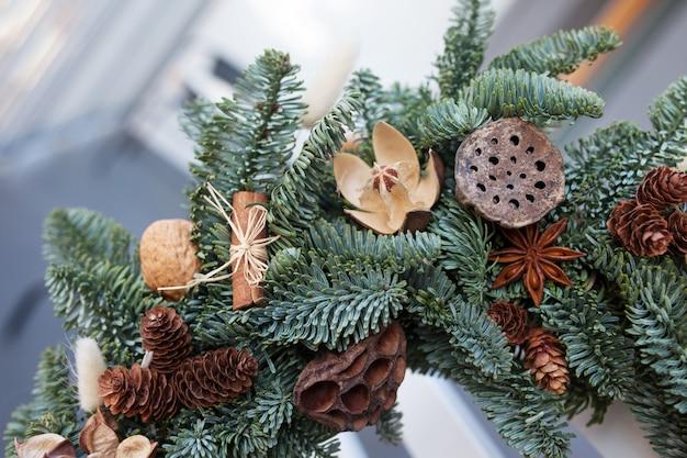 白い椅子の後ろに掛かっている自然なモミの枝で作られたクリスマスリースの詳細。自然の装飾と花輪:バンプ、クルミ、シナモン、コーン。クリスマスの装飾。