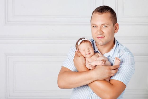 かわいい新生児の女の子を保持している幸せな父。お母さん、お父さん、赤ちゃん。閉じる。父と笑顔の生まれたばかりの赤ちゃんの少女の肖像画。幸せな家族の概念