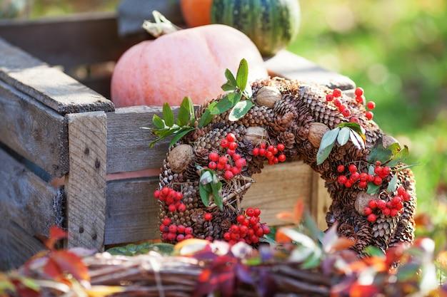 Плетеный венок украшен оранжевыми листьями, осенними ягодами и овощами: тыквы, рябина, орехи, шишки на деревянной коробке. осеннее украшение