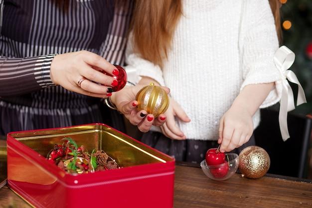 Мать и дочь достают елочные игрушки из коробки