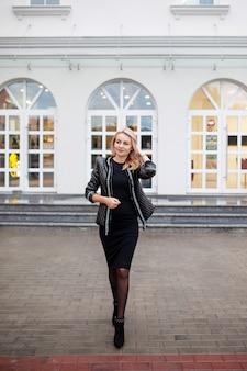 街で楽しんで幸せな美しい女。ファッション女性はハイヒールで通りを歩いています。