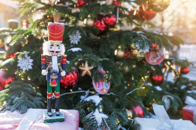Щелкунчик на рождественской ярмарке в зиме москва, россия. украшение адвента и елочка с поделками на базаре. улица рождественский праздник в европе. новогоднее украшение на улице города