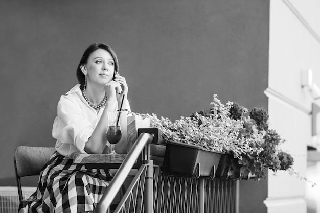 テーブルに座って電話で話している素敵な思いやりのある若い女性。フレッシュジュースとテーブルの上のノートパソコンのガラス。市内のストリートカフェ。黒と白の画像。コピースペース