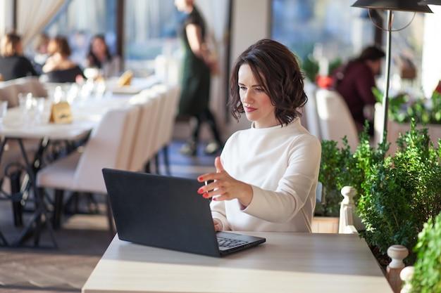 カフェでラップトップで座っている白いドレスの大人のエレガントな実業家。カフェでノートを使用して美しいブルネットの女性。キーボードで入力する中年の女性のショット