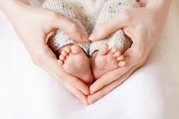母の手で赤ちゃんの足。女性のハート型の手のクローズアップに小さな新生児の足