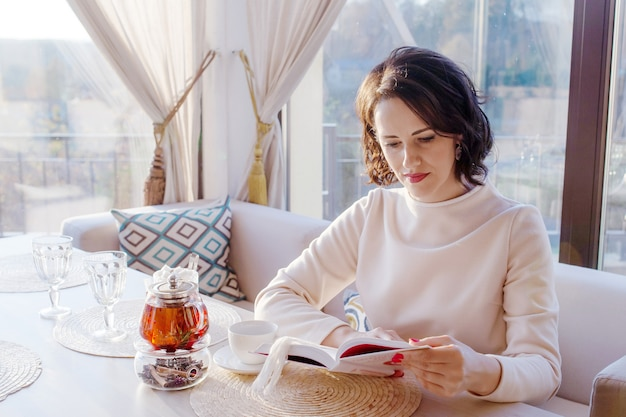 窓の近くの居心地の良いカフェで本を読んで美しい女性。ビジネスウーマンはティーカップで休憩します。スタイリッシュなカフェで明るいライフスタイルの写真。