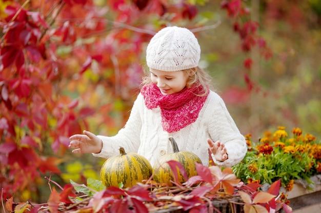 Милая маленькая девочка, играя с тыквами в осенний парк. осенние мероприятия для детей