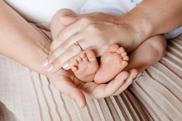 母の手で赤ちゃんの足。女性の形をした手のクローズアップに小さな生まれたばかりの赤ちゃんの足。ママと彼女の子供。幸せな家族の概念。マタニティの美しい概念図
