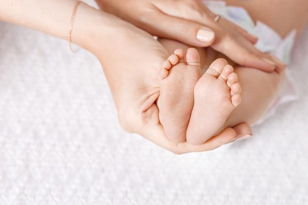 Родитель держит в руках ноги новорожденного. ноги крошечного новорожденного на крупном плане рук.