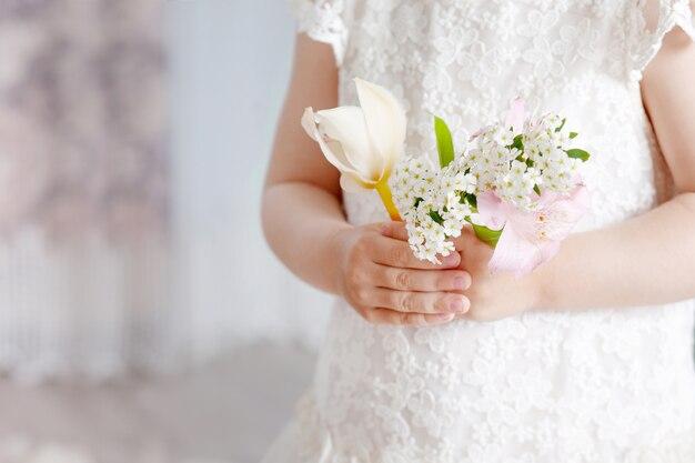 Сладкая девочка держит цветы в руках. крупным планом фото.
