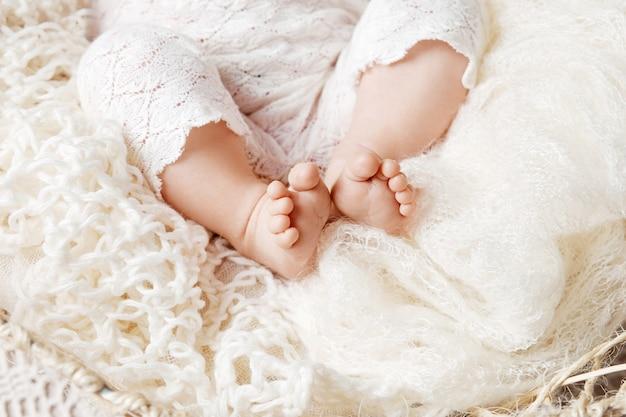 Крупным планом картина ноги новорожденного ребенка в вязаном пледе