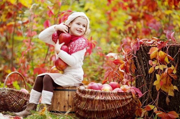 秋の庭でリンゴを保持している美しい少女。 。リンゴの木の果樹園で遊ぶ少女。秋の収穫で果物を食べる幼児。子供のための屋外の楽しみ。健康的な栄養