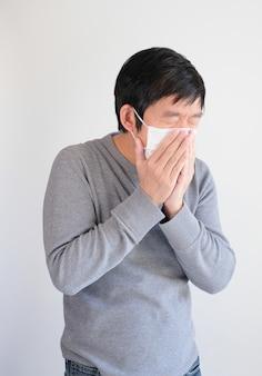 くしゃみをする防護マスクを着た男