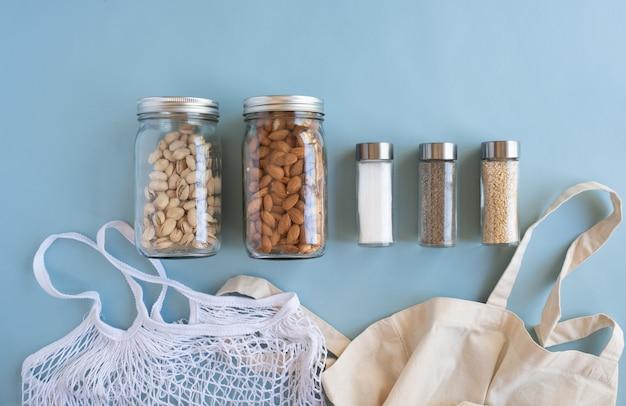 Ноль отходов жизни. хлопчатобумажная сетка с орехом, специи в устойчивой стеклянной банке на синем фоне