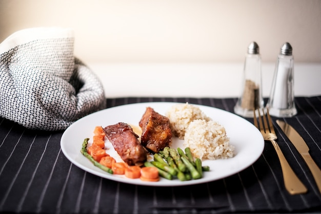 健康的な食事。ダイエット食品の夕食。豚カルビとインゲン、ニンジン、キノア。