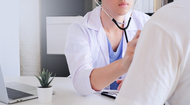 若い医者は診療所で患者を診断します。