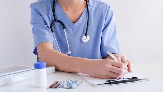 働く医師と病院。青いユニフォームで処方を処方します。