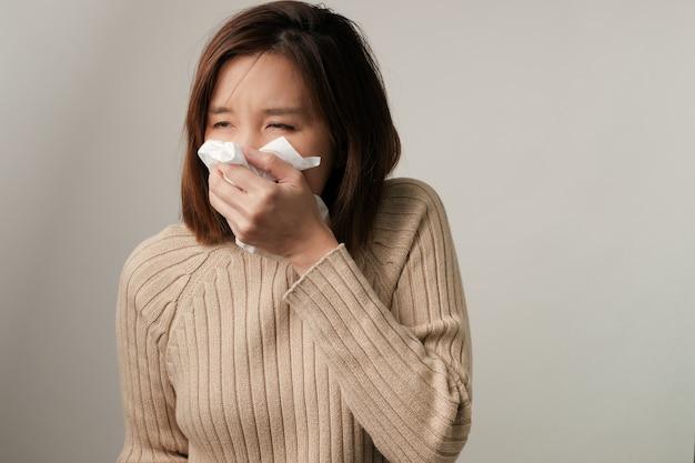 Больная азиатская женщина, чихающая. концепция болезни и болезни