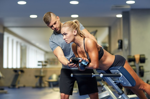 ジムで筋肉を屈曲するパーソナルトレーナーを持つ女性