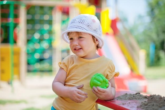 Ребенок, играющий в песочнице