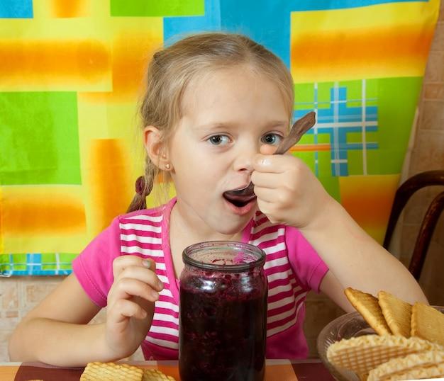 小さな女の子がジャムを食べる
