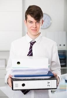 Веселый стажер, держащий документы