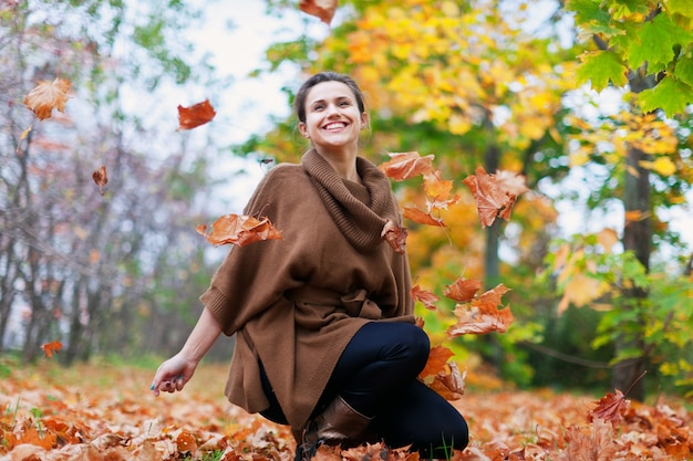 Счастливая девушка бросает кленовые листья