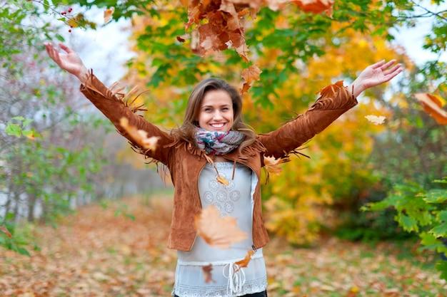 幸せな女の子が楓の葉を投げる