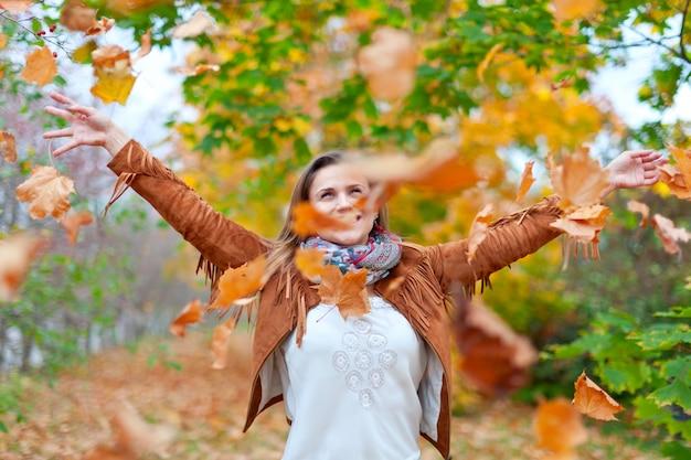 幸せな女性が葉を投げる
