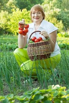 Зрелая женщина в овощном саду
