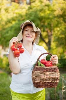 Женщина с корзиной собранных овощей