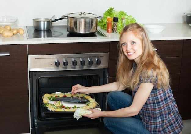 海の魚とジャガイモをパンの上で料理する笑顔の主婦