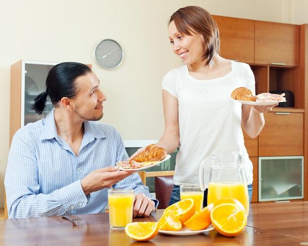 笑顔の女性はクロワッサンを提供し、スクランブルエッグ彼女の男