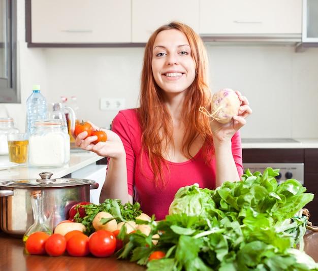 Женщина со свежими овощами в кухне