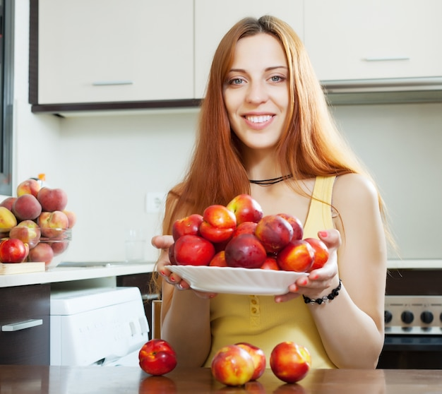 Счастливая молодая женщина с нектаринами