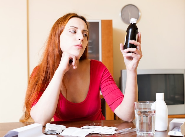 家庭のマニュアルで薬を読んでいる赤毛の女性