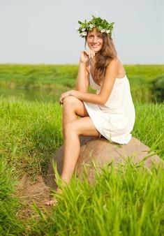 女の子は畑の石に座っている